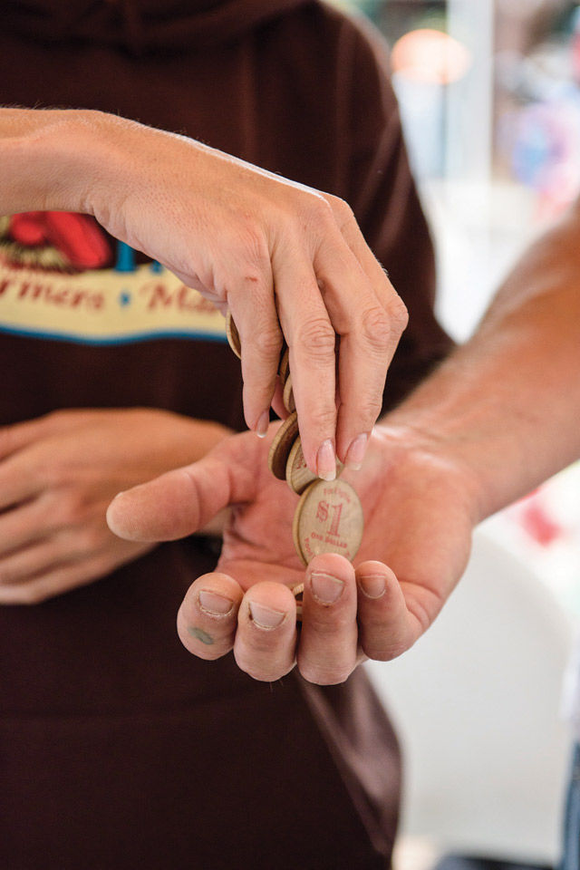 The Taos Farmers' Market gives out wooden and metal tokens to use as part of the Double Up Food Bucks program. The program gives people on SNAP double the money when spent on New Mexico-grown produce. (Katharine Egli)